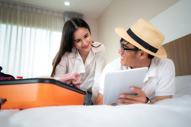 De gelukkige koffer van de paarverpakking op bed in slaapkamer en het liggen digitale tablet voor zoekreis reis online. aziatische backpacker reizen levensstijl concept. Premium Foto