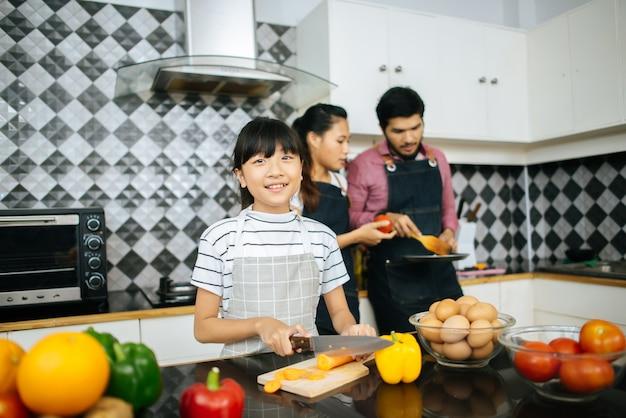 De gelukkige mama onderwijst haar dochter die groente hakt die ingrediënten voorbereidt Gratis Foto