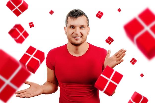De gelukkige mens in rode t-shirt is gelukkig van giften die op wit vallen Premium Foto
