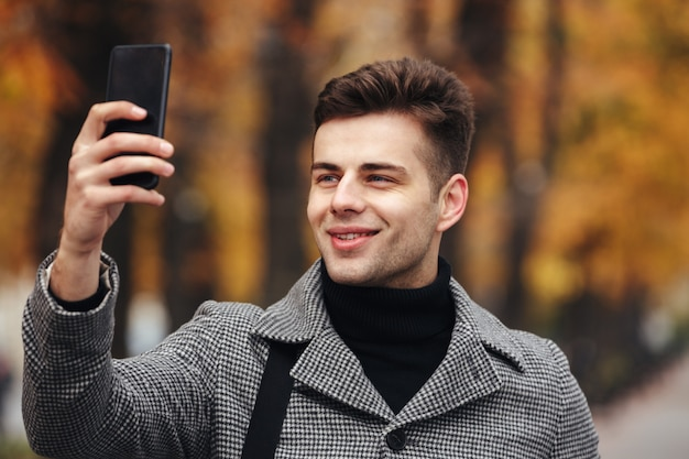 De gelukkige mens kleedde warm het nemen van foto van aard of het maken van selfie gebruikend zwarte smartphone, terwijl het lopen in park Gratis Foto