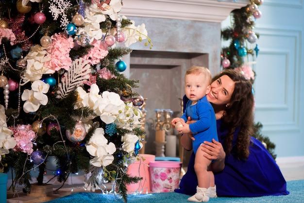 De gelukkige moeder en de baby vieren kerstmis. nieuwjaars vakantie. Premium Foto