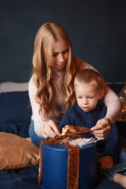 De gelukkige moeder en de zoon openen de giftdoos Premium Foto