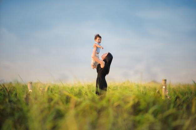 De gelukkige moeder houdt gelukkig weinig baby in het groene padieveld aan de kant van het land van thailand. Premium Foto