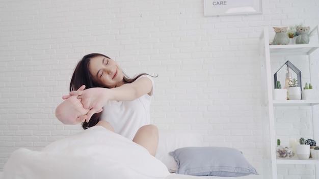 De gelukkige mooie aziatische vrouw ontwaakt, glimlacht en uitrekt haar wapens in haar bed in de slaapkamer. Gratis Foto