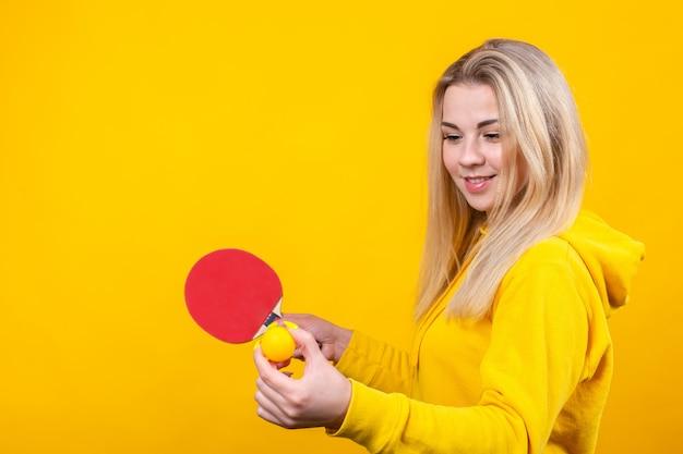De gelukkige mooie jonge blondevrouw in toevallige gele sportieve kleren spelen pingpong, houdend een bal en een racket. Premium Foto