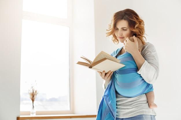 De gelukkige mooie moeder nestelt zich haar slapend kind aan borst en het lezen van boek over kindeducatie in heldere gezellige ruimte voor venster. familiemomenten. Gratis Foto