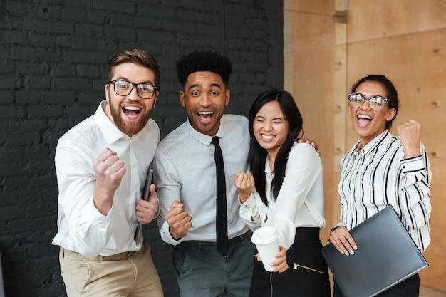 De gelukkige opgewekte jonge bedrijfscollega's maken winnaargebaar. Gratis Foto