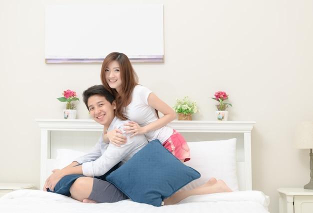 De gelukkige paren glimlachen en zitten op bed, Premium Foto