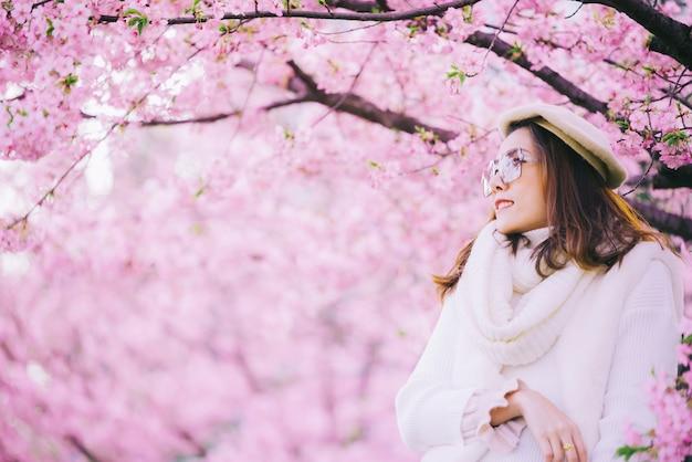 De gelukkige reisvrouw en de glimlach met sakurakers komen boom op vakantie tot bloei terwijl aziatische de lente ,. Premium Foto
