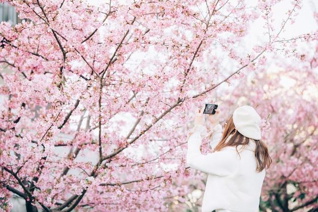 De gelukkige reisvrouw en neemt een foto van de kers van sakura bloeit boom op vakantie terwijl de lente Premium Foto