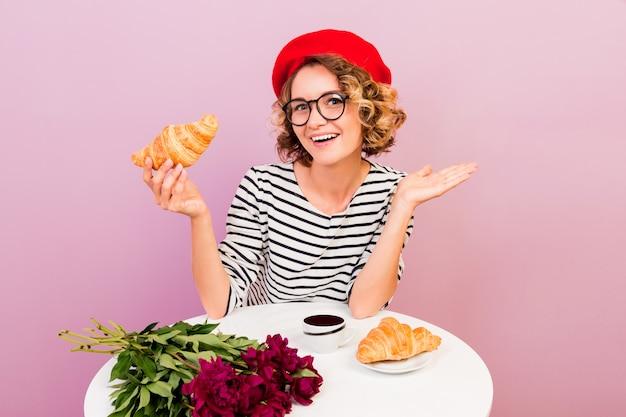 De gelukkige reizende vrouw die in frankrijk croissans met koffie eten, zit bij de lijst aangaande roze. Gratis Foto