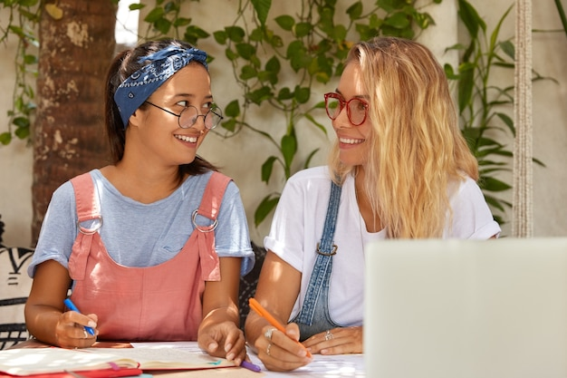 De gelukkige tevreden glimlachende tienerpennen van de studentengreep, bereiden zich voor op het schrijven van cursusdocument Gratis Foto