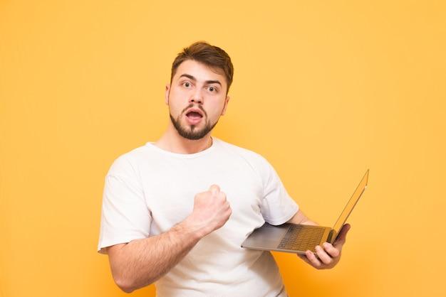 De gelukkige tiener in een wit t-shirt houdt de laptop in zijn handen Premium Foto