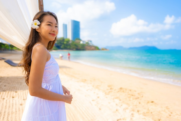 De gelukkige vrije tijd van de portret mooie jonge aziatische vrouw gelukkige op het strandoverzees en de oceaan Gratis Foto