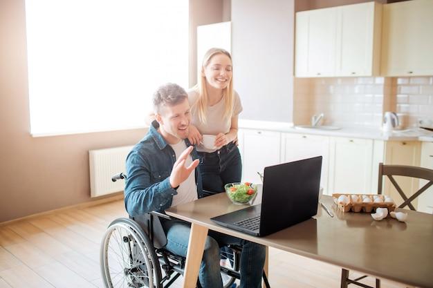 De gelukkige vrolijke jonge mens zit bij lijst en kijkt op laptop. man met handicap en inclusiviteit. jonge vrouwentribune trouwens. film kijken op lpatop. Premium Foto