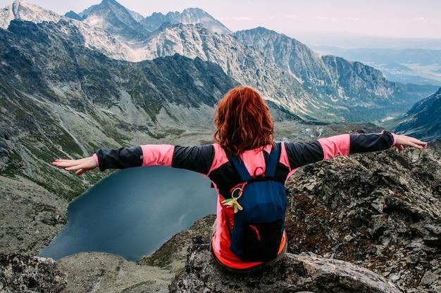 De gelukkige vrouw geniet van mening van meer in de de zomerbergen Premium Foto