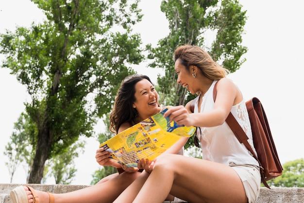 De gelukkige vrouwelijke kaart die van de toeristenholding ter beschikking elkaar bekijken Gratis Foto