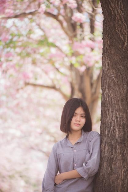 De gelukkige vrouwreiziger ontspant zich vrij met kersenbloesems of sakura-bloembomen op vakantie Gratis Foto