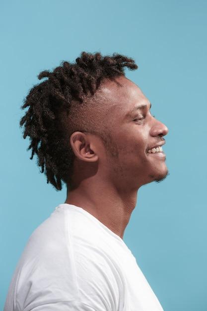 De gelukkige zaken afro-amerikaanse man staan en glimlachen tegen blauw. Gratis Foto
