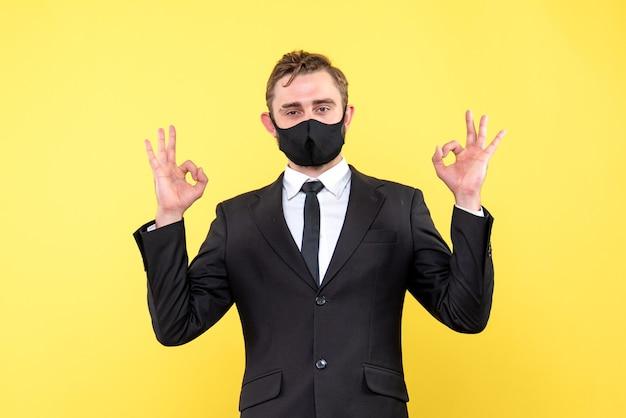De gelukkige zakenman maakt dubbel ok handteken op geel Gratis Foto