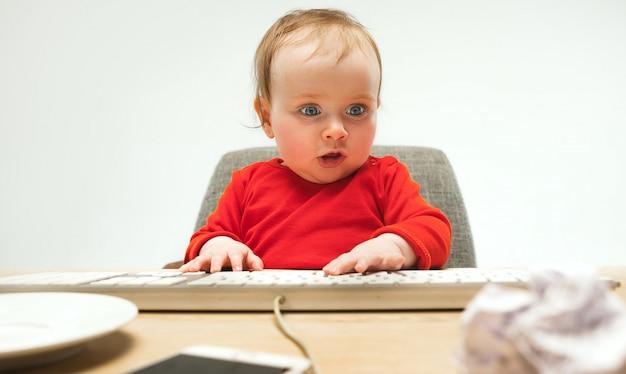 De gelukkige zitting van de het meisjespeuter van de kindbaby met toetsenbord van computer die op een witte achtergrond wordt geïsoleerd Gratis Foto