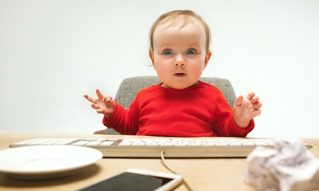 De gelukkige zitting van de het meisjespeuter van de kindbaby met toetsenbord van de computer die op een wit wordt geïsoleerd Gratis Foto