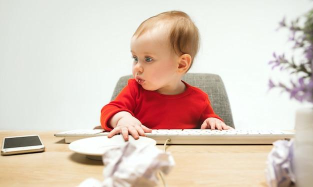 De gelukkige zitting van de het meisjespeuter van de kindbaby met toetsenbord van de computer op een wit Gratis Foto