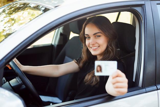 De gelukkige zitting van de studentenbestuurder in de moderne zilveren auto en het tonen van rijbewijs Premium Foto