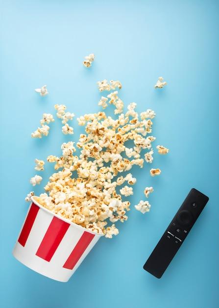 De gemorste popcorn op een blauwe achtergrond met tv verwijdert. Premium Foto