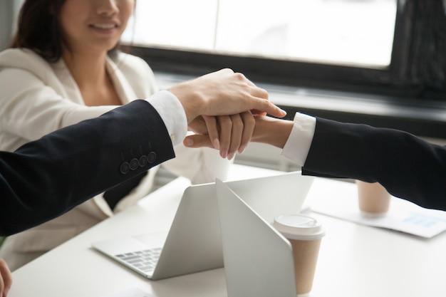 De gemotiveerde bedrijfsmensen brengen samen handen, het concept van de loyaliteitsovereenkomst, close-up Gratis Foto