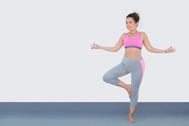 De geschikte vrouw kleedde zich voor sport in yogahouding, die op wit wordt geïsoleerd. Premium Foto
