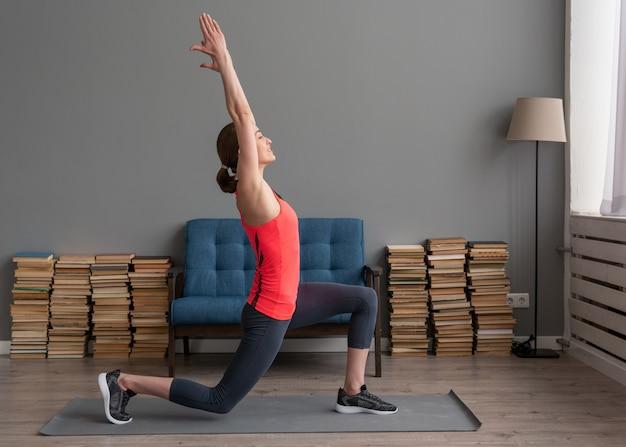 De geschiktheidsvrouw die voorzijde doen valt oefening voor been het uitrekken zich op mat thuis uit Premium Foto