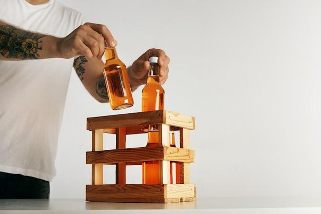 De getatoeëerde man dient in lege witte t-shirt flessen met cider in een houten kist te zetten die op wit wordt geïsoleerd Gratis Foto