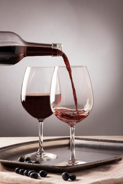 De gietende vloeistof van de rode wijnfles in glas Gratis Foto