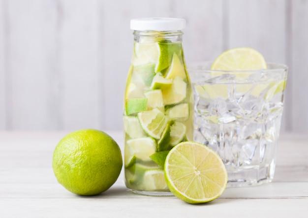 De glasfles van kalk snijdt nog fruitwater en ruwe limoenen op witte houten met glas en ijsblokjes Premium Foto