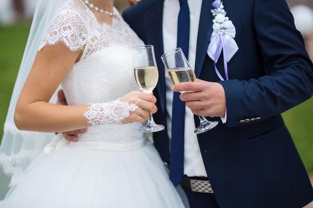 De glazen van de bruid en bruidegom dienen in close-up met champagne in Premium Foto