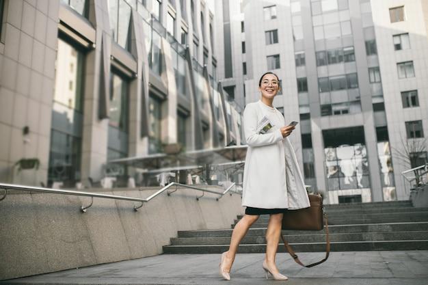 De glimlachende aantrekkelijke aziatische bedrijfsvrouw in glazen met een krant ontmoet een collega dichtbij bureaucentrum Premium Foto