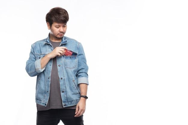 De glimlachende aziatische mens die een creditcard houdt, zet in de zak van de spijkerbroek Premium Foto