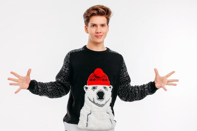 De glimlachende jonge mens in comfortabel draagt sweater omhelzingen op witte achtergrond Premium Foto