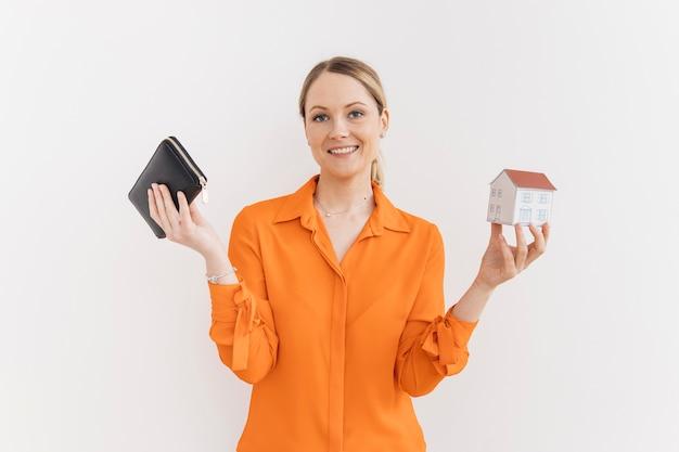De glimlachende jonge portefeuille van de vrouwenholding en miniatuurhuismodel dat op witte muur wordt geïsoleerd Gratis Foto