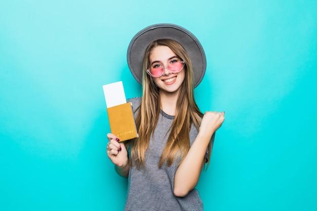 De glimlachende jonge tienerdame houdt haar paspoortdocumenten met kaartje in haar handen die op groene studiomuur worden geïsoleerd Gratis Foto