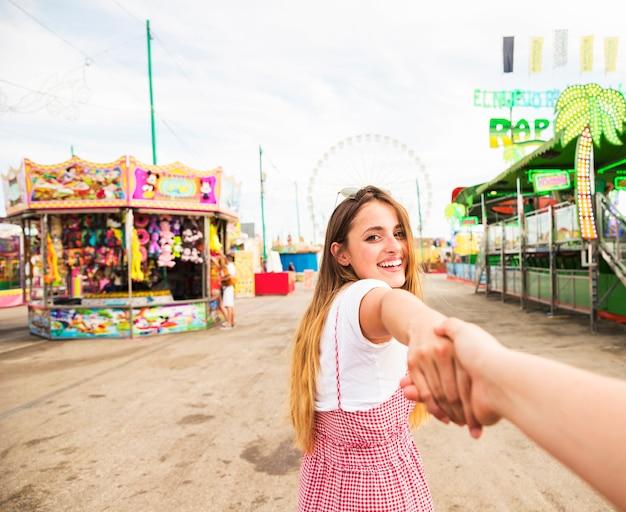 De glimlachende jonge vrouw houdt de hand van haar vriend lopend in het pretpark Gratis Foto
