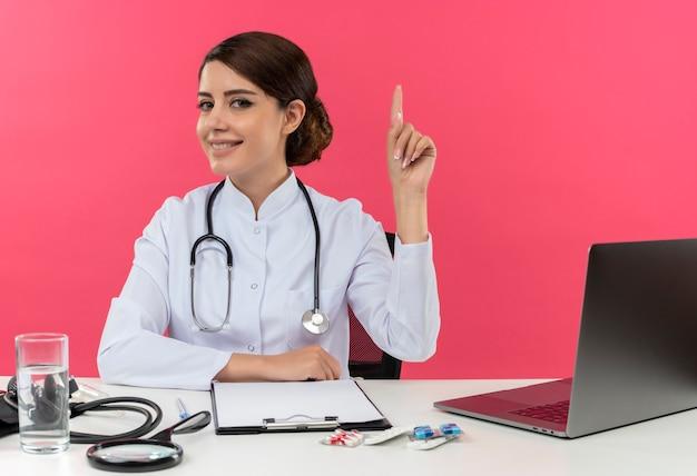De glimlachende jonge vrouwelijke arts die medische kleed met stethoscoop draagt die aan bureau werkt op computer met medische hulpmiddelen wijst met exemplaarruimte omhoog Gratis Foto