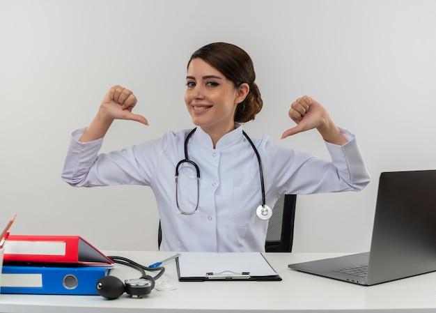 De glimlachende jonge vrouwelijke arts die medische mantel met stethoscoop draagt die aan bureauwerk op computer met medische hulpmiddelen zit, wijst naar zichzelf met exemplaarruimte Gratis Foto