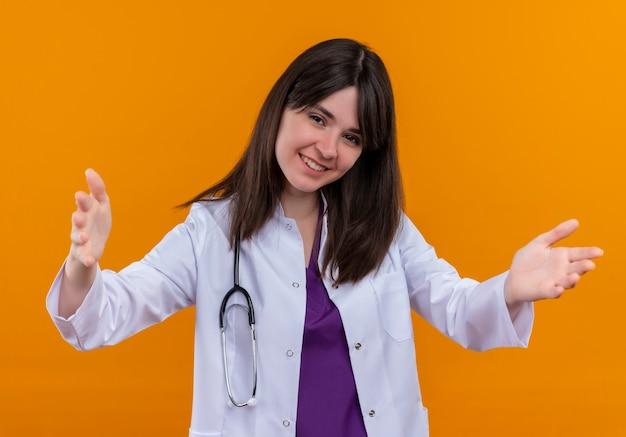 De glimlachende jonge vrouwelijke arts in medisch kleed met stethoscoop houdt beide handen open op geïsoleerde oranje achtergrond met exemplaarruimte Gratis Foto