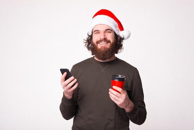 De glimlachende knappe mens houdt een kop om te gaan en zijn telefoon over witte achtergrond. Premium Foto