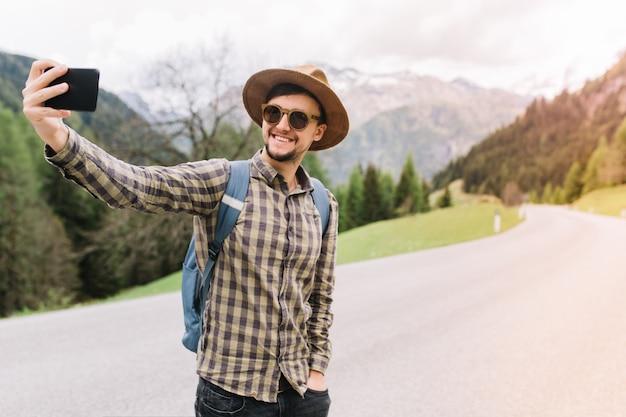 De glimlachende mens in bruine hoed die zich met hand in zak bevindt en selfie maakt terwijl de auto op weg vangt Gratis Foto