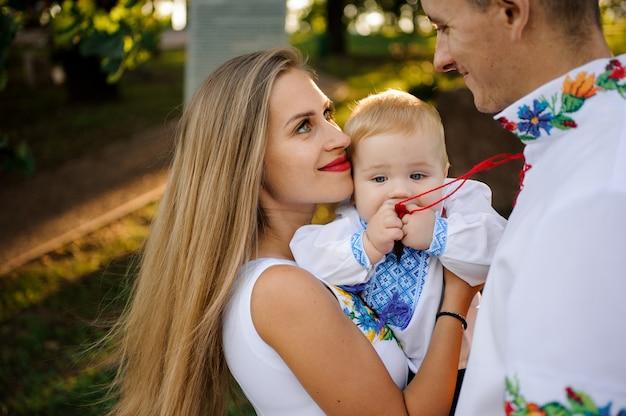 De glimlachende moeder en de vader die op handen houden een babyjongen kleedde zich in het geborduurde overhemd Premium Foto