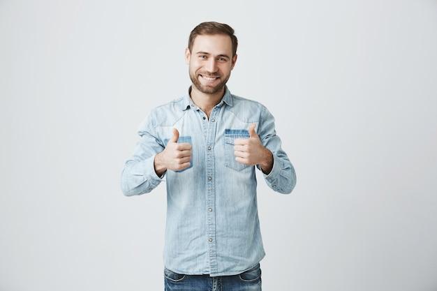 De glimlachende optimistische mens toont duim-omhoog, keurt goed of adviseert Gratis Foto