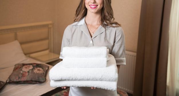 De glimlachende stapel van de professionele kamermeisjesholding van schone handdoeken in slaapkamer Gratis Foto